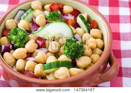 Chickpea salad in brown bowl on checkered tablecloth