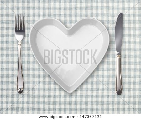 Table appointments with heart-shaped plate. Template with empty plate fork knife on retro tablecloth.