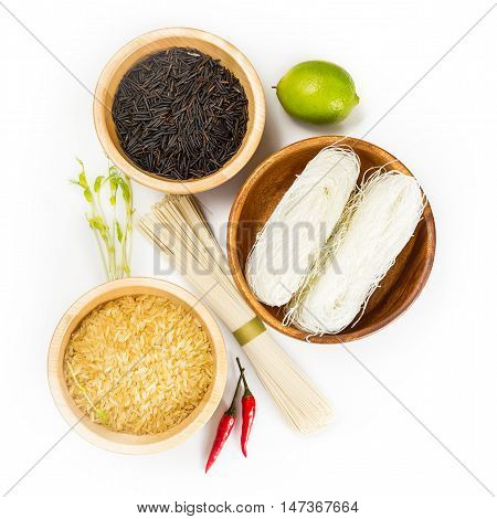 Wooden bowls with organic wild rice, rice noodles, red hot pepper and lime on white background