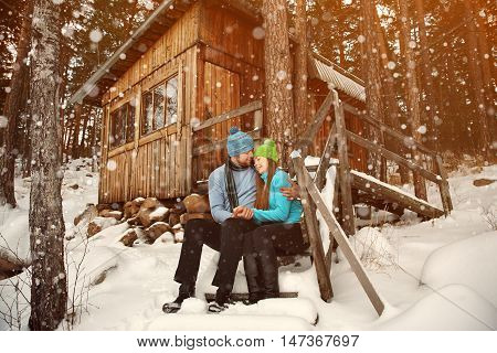 man and woman sitting on the porch of a house. young happy couple in love outdoors in the winter
