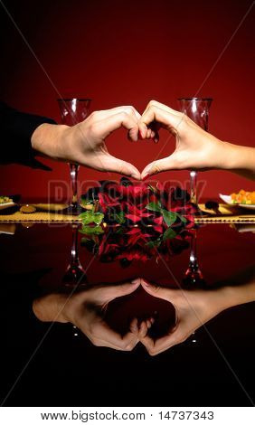 Close-up do jovem casal na mesa do restaurante com as mãos fazendo uma forma de coração