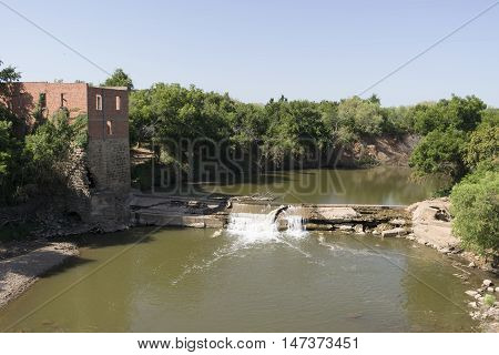 Abandoned and empty water mill next to a small waterfall on a tree lined river on a sunny day.