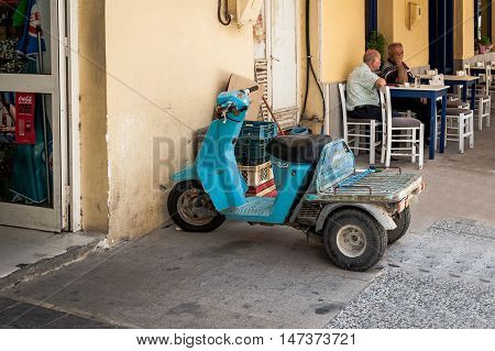 PALEOCHORA, CRETE, GREECE - JUNE 2016: Cargo motorcycle stays parked near shop while driver is sitting in cafe in Paleochora town on Crete island, Greece