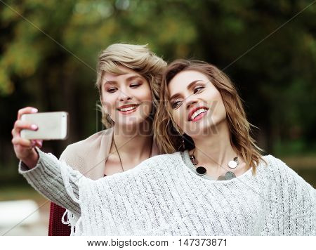 life style, happiness, emotional and people concept: Friends making selfie. Two beautiful young women making selfie in autumn park.