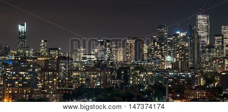Urban lighted landscape and skyline of Toronto.   A rooftop panoramic of urban streets, homes, condos, and office towers on a hot, humid August night in The capitol of Ontario, Canada,