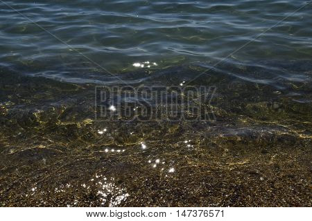 The transparent sea water near the shore. Visible stones and sand at the bottom through the water.
