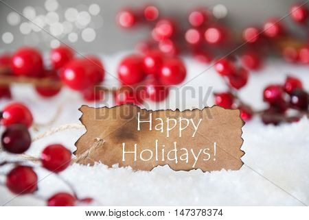 Burnt Label With English Text Happy Holidays. Red Christmas Decoration On Snow. Cement Wall As Background With Bokeh Effect. Card For Seasons Greetings