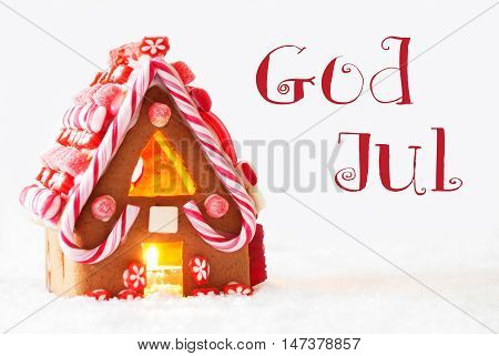 Gingerbread House In Snowy Scenery As Christmas Decoration With White Background. Candlelight For Romantic Atmosphere. Swedish Text God Jul Means Merry Christmas