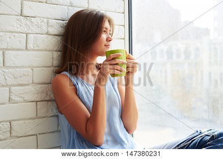 Caucasian girl in pensive mood seemed lost in thought while sitting on the window-sill  and drinking a cup of coffee