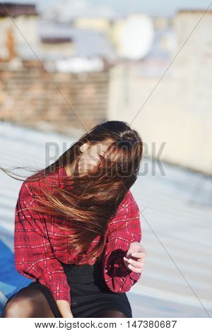 Young teenager girl with long hair flying in the wind sitting on the roof of city building