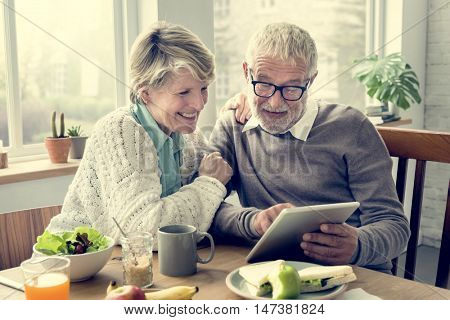 Senior Adult Holding Tablet Reading Concept