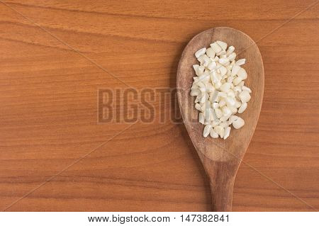 White grated corn kernels into a spoon over a wooden table