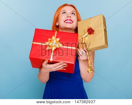 People celebrating holidays love and happiness concept - happy joyful red hair girl with gift boxes studio shot on blue background