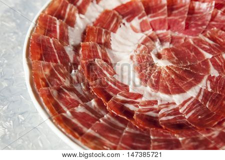 Circular decorative arrangement of iberian cured ham on plate. Selective focus point.