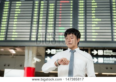 Asian young businessman looking at his watch in front of airport timetable at the airport terminal. Business travel concept.