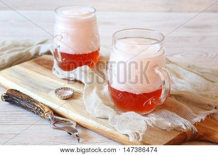 Two mugs of light fruit beer with foam cap
