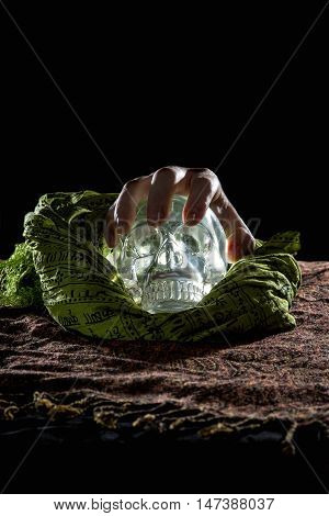 Creepy hand grabbing a crystal skull in a dark background
