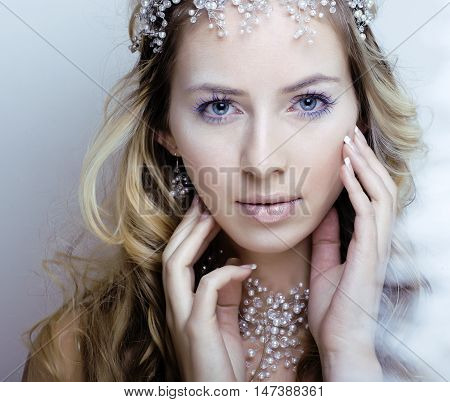 beauty young snow queen with hair crown on her head, complicate hairstyle, winter concept close up