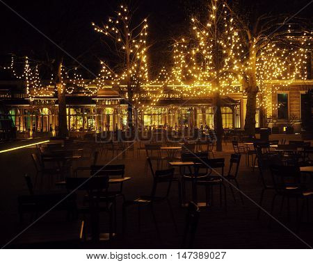 empty night restaurant, lot of tables and chairs with noone, magic fairy lights on trees like christmas