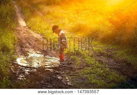 Boy Playing In Puddle In Forest