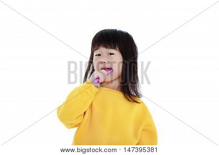 Closeup cute asian girl in pajamas with a toothbrush in hand and brush teeth oral health concept. Isolated on white background. Sleepy chinese child waking up early in the morning.