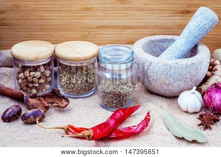 Assortment Of Spices Ingredients For Thai Popular Food Red Curry With Mortar Set Up On Wooden Table.