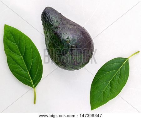 Healthy Food Concept . Closeup Fresh Avocado And Leaves On Marble Background.