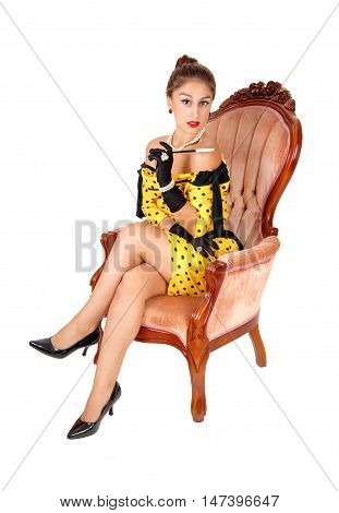 A lovely young woman sitting in a yellow dress in a pink armchair holding a long cigarette holder isolated for white background.