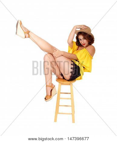 A beautiful young woman sitting on a chair in black shorts and yellow blouse lifting up one leg isolated for white background.