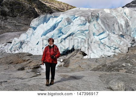 Treker standing near a glacier in the Norwegian mountains. Nigardsbreen glacier, Norway. September 2015