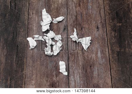 White paper sheet  note rip Pieces and crumpled on a wooden floor  : with copy space for add text above and may be used as background :
