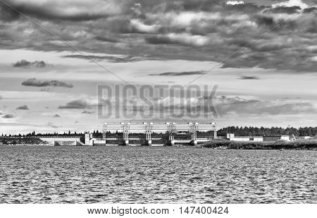A hydro electric station under cloudy sky in black and white