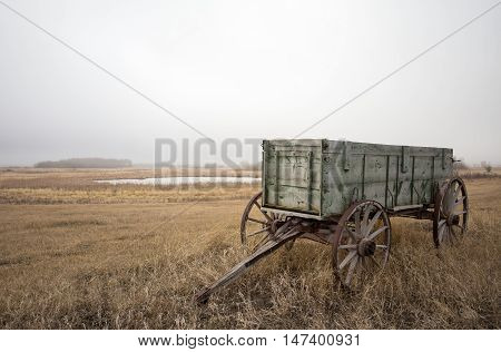 Vintage weathered wooden horse drawn wagon beside a field in a brown spring landscape