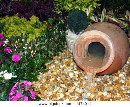 Terra Cotta Urn Fountain In Rock And Flower Garden