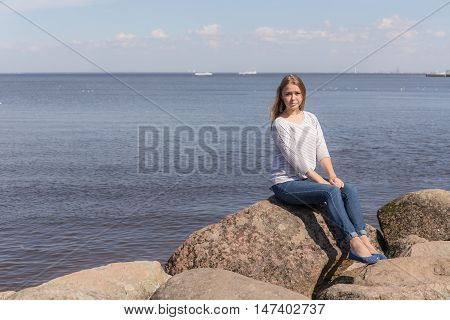 girl on the rocks by the sea shore