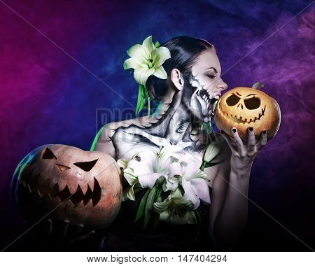 Young attractive girl with creative make-up for Halloween. Portrait close-up pumpkins. She bites pumpkin. Mysterious and frightening image of lilies. Witchcraft. Horrible. Jack-o'-lantern