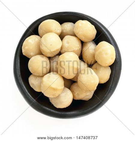 Macadamia nuts in rustic black bowl.  Top view, isolated on white.