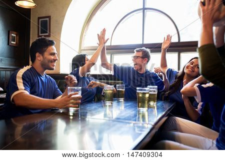 sport, people,  friendship and entertainment concept - happy football fans or friends drinking beer, making high five and celebrating victory at bar or pub
