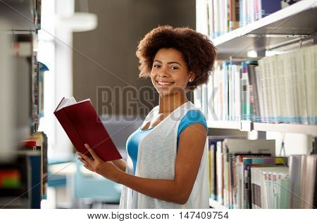education, high school, university, learning and people concept - happy smiling african american student girl reading book at library