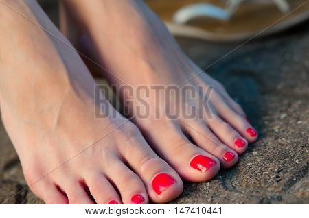 Female feet with red nail polish barefoot on the sidewalk
