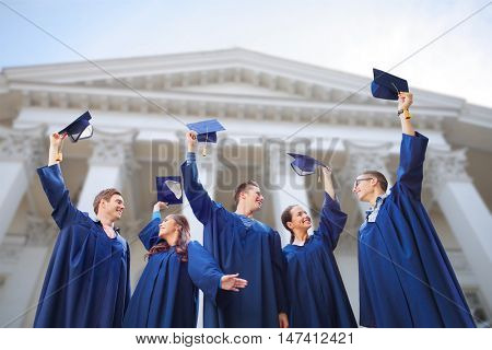 education, graduation and people concept - group of smiling university graduates in gowns waving mortarboards outdoors