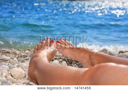 Pies de mujer hermosa en la playa