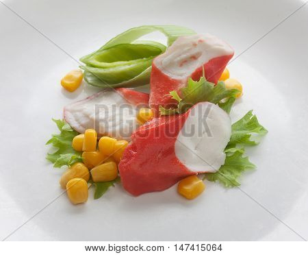 Crab meat with fresh green lettuce and corn on the plate