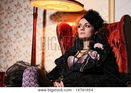 Beautiful fashion model sitting on a luxury sofa