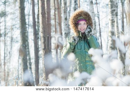 Cheerful young woman is holding woolly mittens near her head in winter forest outdoors