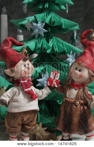 Christmas Elfs Boy And Girl Giving A Present Under Christmas Tree  (vertical)