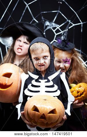 Portrait of three Halloween children with pumpkins looking at camera with fearful grimaces