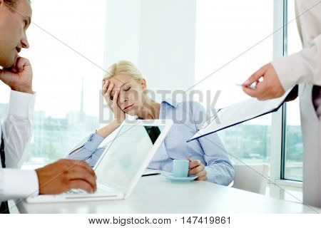 Young woman falling asleep while working in office