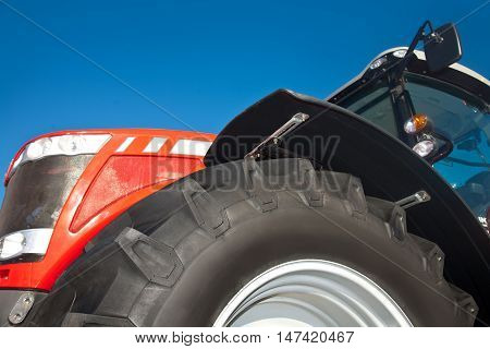 Red tractor against the clear blue sky close-up