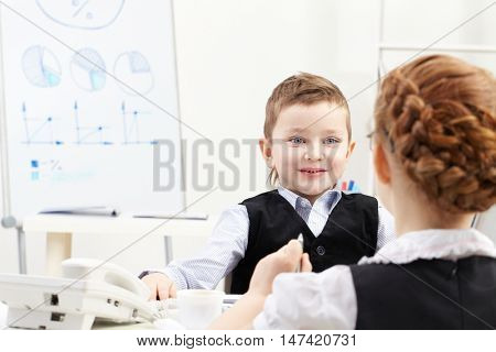 Little boy communicating with a girl in office